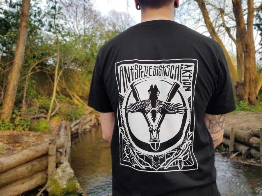 Photo of a person wearing a tshirt with their back facing the camera wearing a black tshirt with a fullsize print